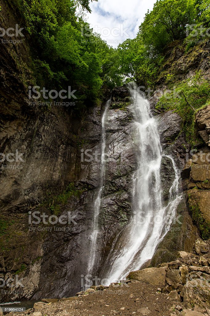 small waterfall in mountains stock photo