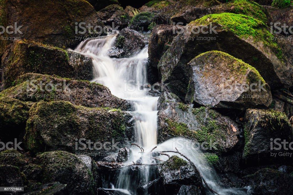 Small Waterfall with water running through  rocks stock photo