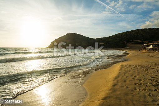 Small waves by La Speranza beach shore at sunset. Sardinia, Italy
