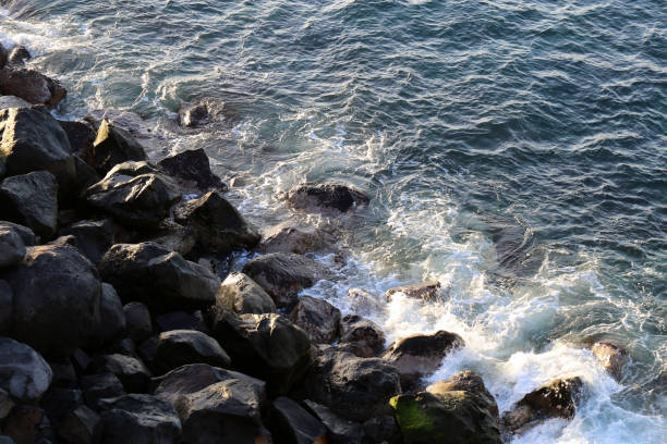 Small Waves Hitting Rock on a Beach Located in Funchal, Madeira stock photo