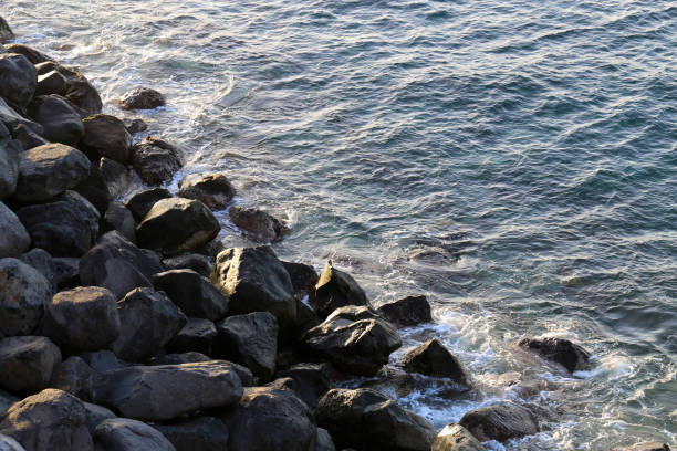 Small Waves of the Ocean are Hitting Rocks in Madeira stock photo