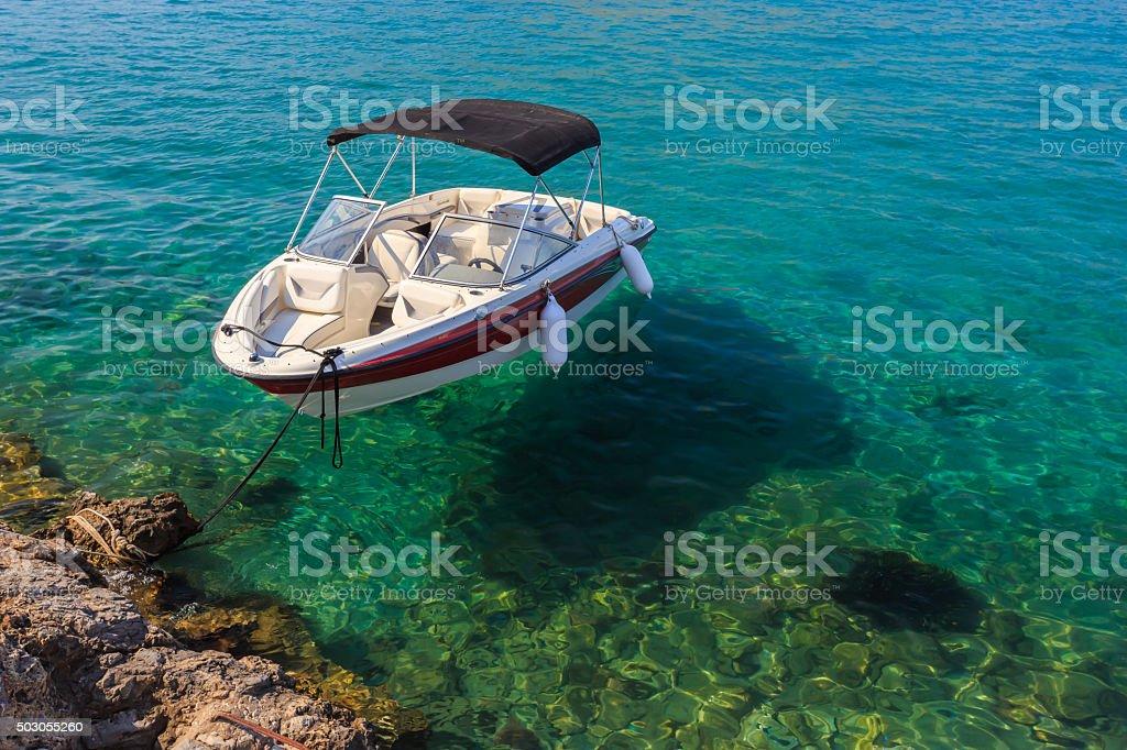 Kleines weißes Boot floating in klarem Wasser nahe der shore – Foto