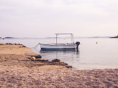 A small white boat moored on the shore in Pakostane in Croatia. In the upper part of the frame there is space to put an inscription