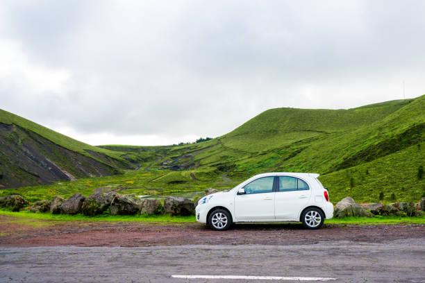 kleine weiße auto stehen am straßenrand - motionless in white stock-fotos und bilder
