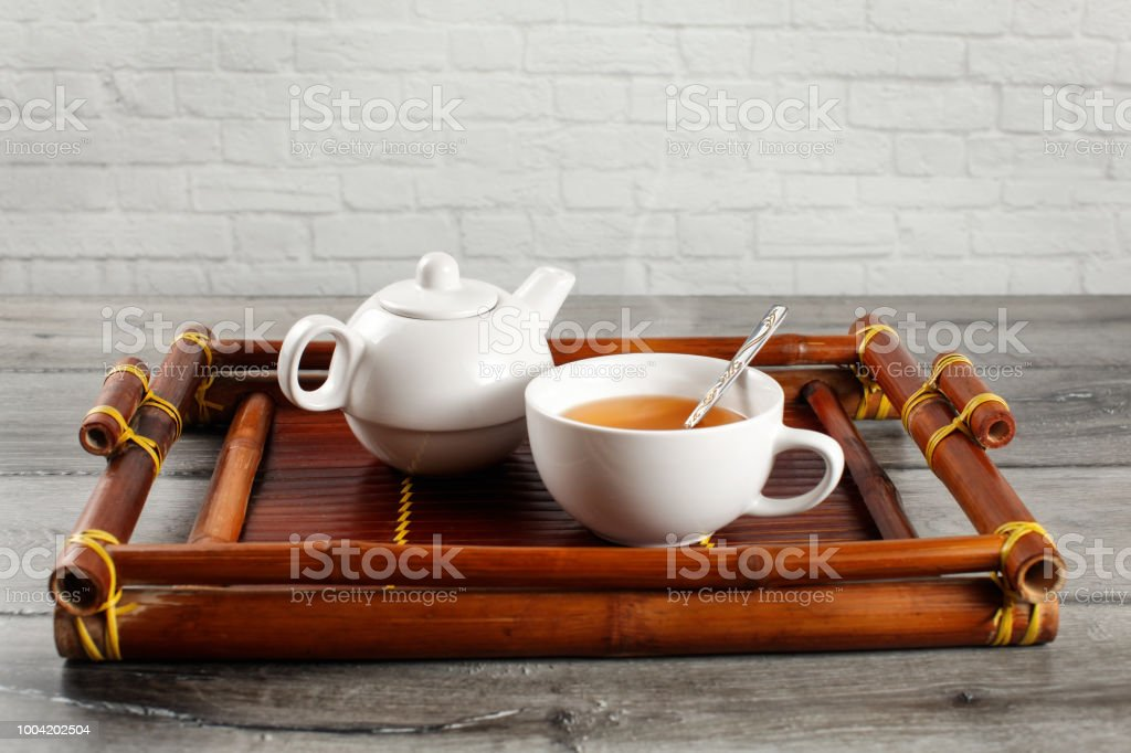 Small white ceramic teapot and cup of hot steaming black tea with...