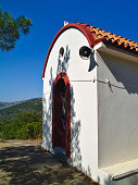Small white chapel with vivid paint colors under clear blue sky.