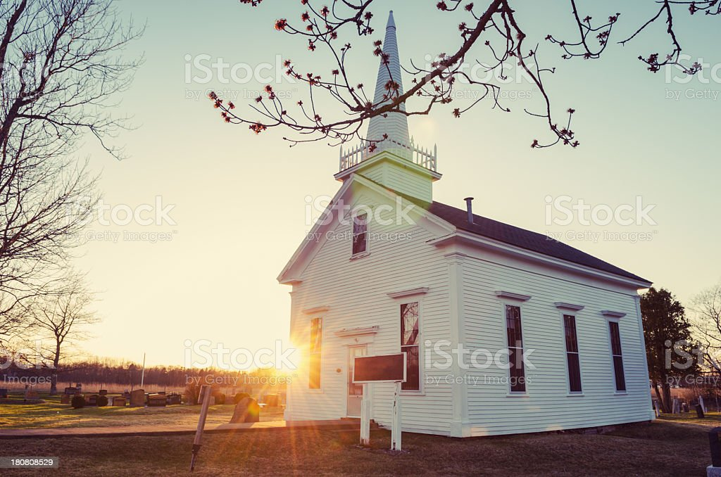 Small white church at sunrise in winter stock photo