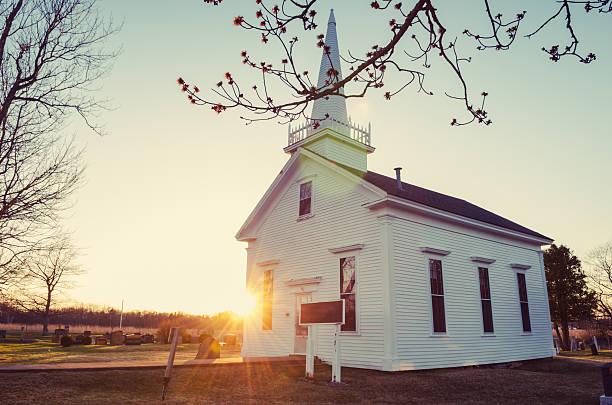 Small white church at sunrise in winter stock photo