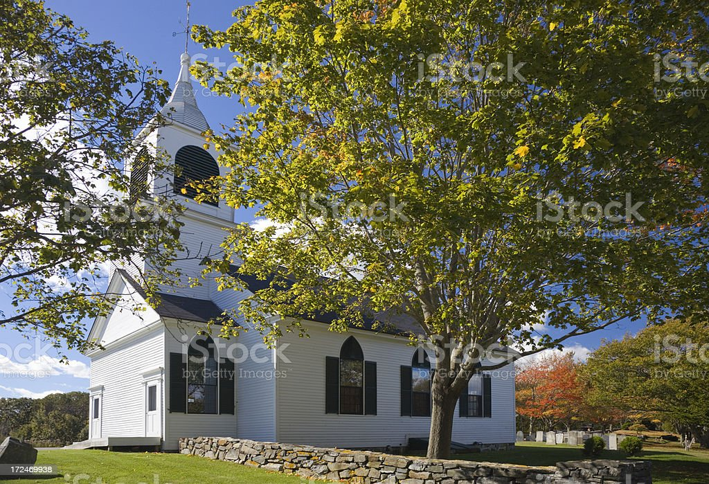 Small white church in Maine with autumn colored trees royalty-free stock photo