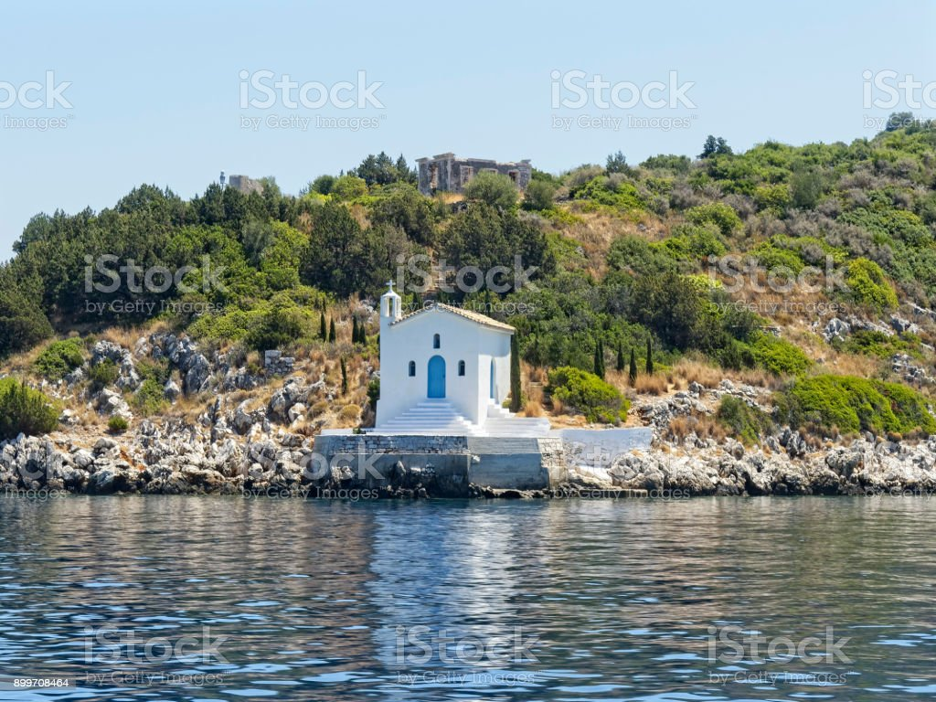 Small white church on the shore of the Ionian sea stock photo