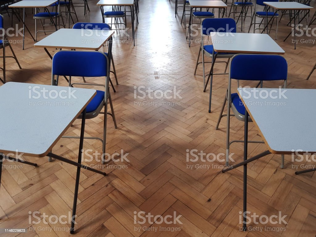 Small white exams desks in a hall