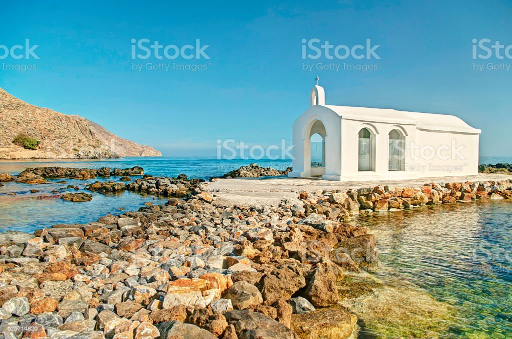 small white Greek church on a tiny island in sea stock photo