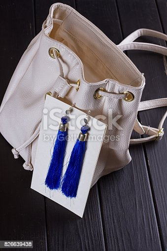 istock small white leather woman's backpack and blue earrings of thread 826639438