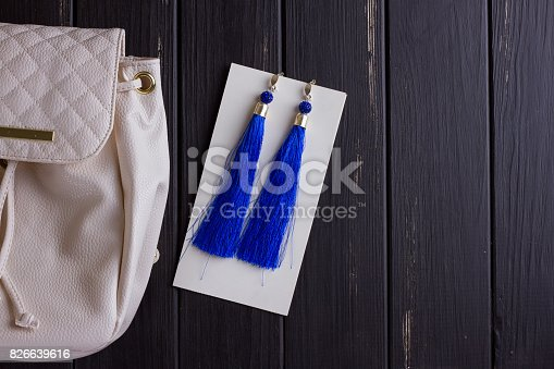 istock small white leather woman's backpack and blue earrings of thread 826639616