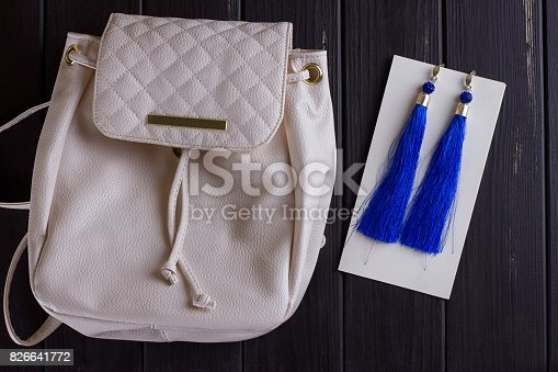 istock small white leather woman's backpack and blue earrings of thread 826641772