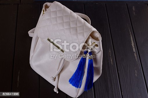 istock small white leather woman's backpack and blue earrings of thread 826641996