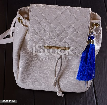 istock small white leather woman's backpack and blue earrings of thread 826642104