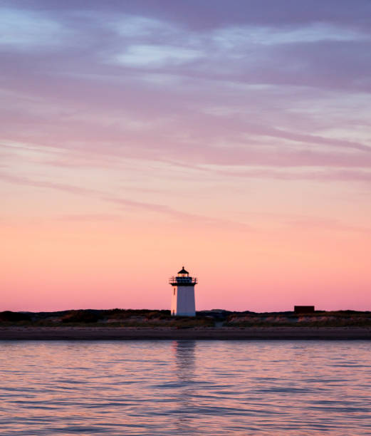 A small white lighthouse is pictured against a beautiful pink and purple sunset from a boat at sea A small square lighthouse sits on a beach. Behind it, the sky is cast pink and purple by the setting sun. In the foreground there is water. cape cod stock pictures, royalty-free photos & images