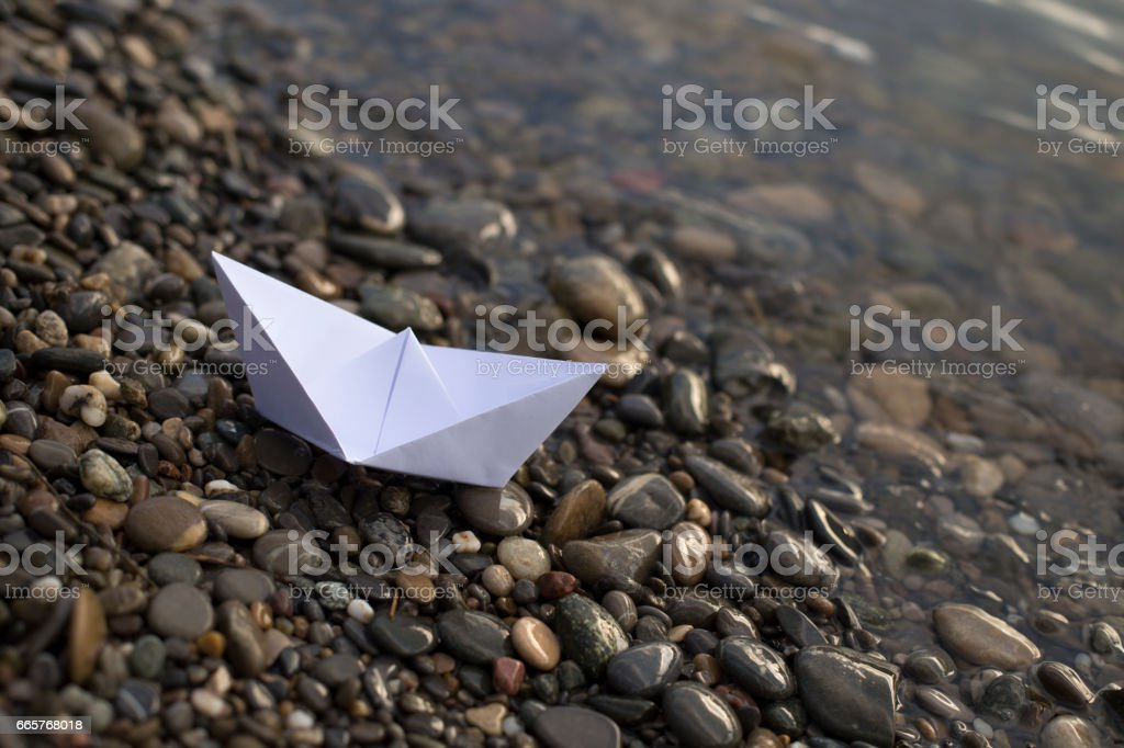 Small white paper ship on a river bank stock photo