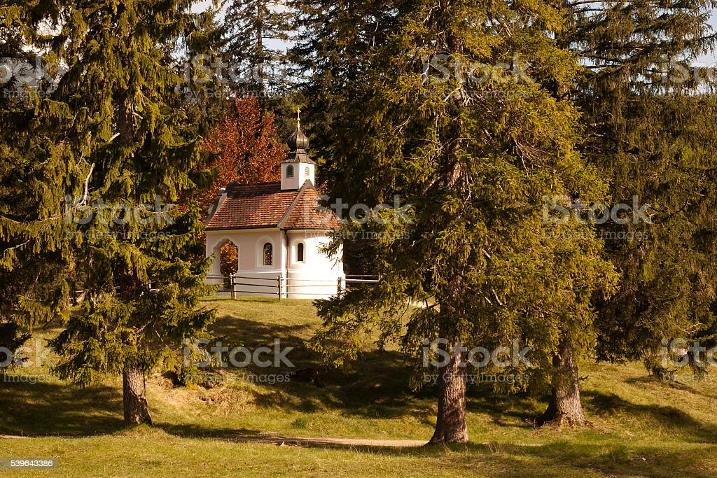 Small white pink chapel among trees near Mittenwald in Bavaria stock photo