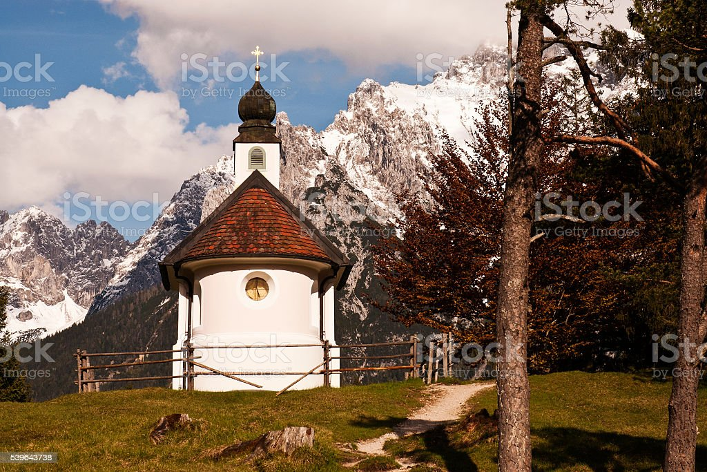 Small white pink chapel and majestic alpine landscape stock photo