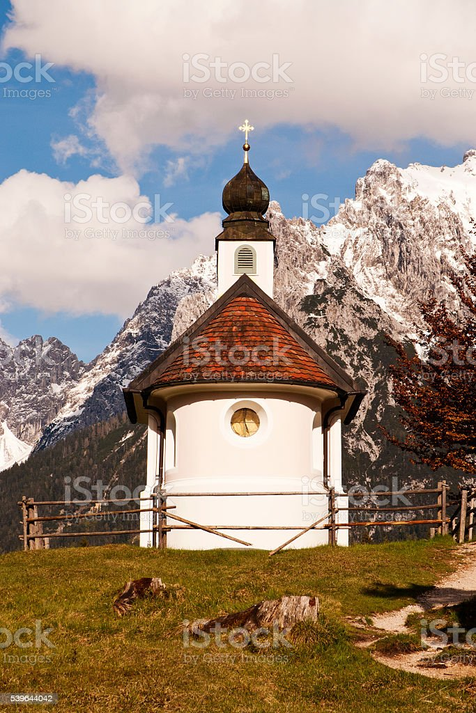 Small white pink chapel and majestic alpine landscape under clouds stock photo