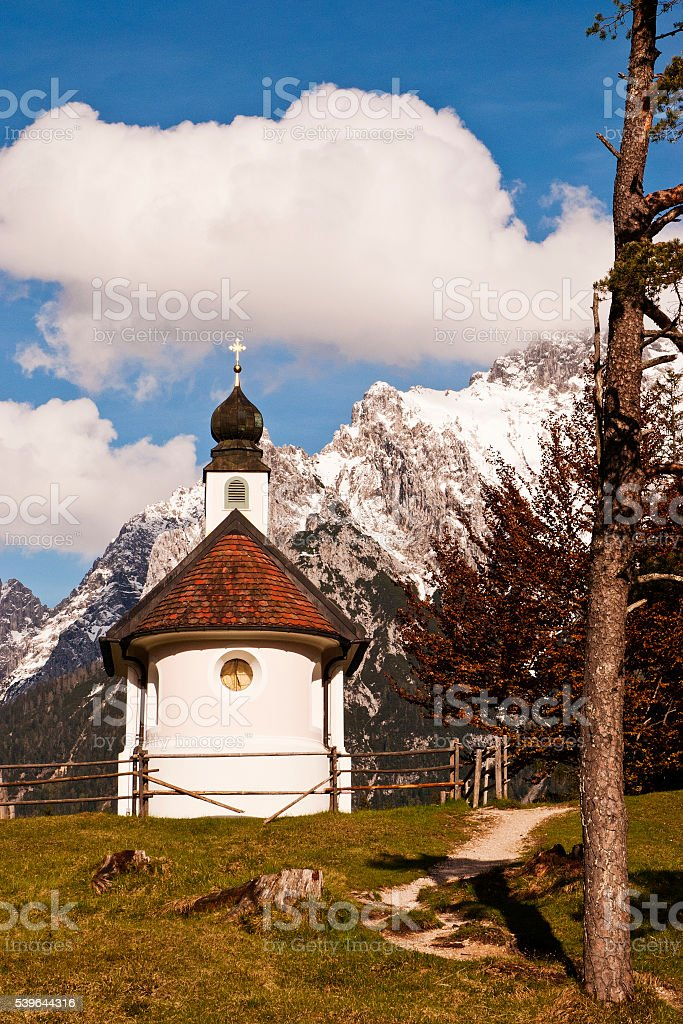 Small white pink chapel and majestic Karwendel landscape under clouds stock photo