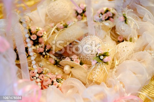 155315629istockphoto Small white pouches with with flowers in the basket. Pouches with gifts for guests at the wedding. 1097478334