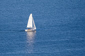 A small white sailing ship on the blue water with reflection (copy space)