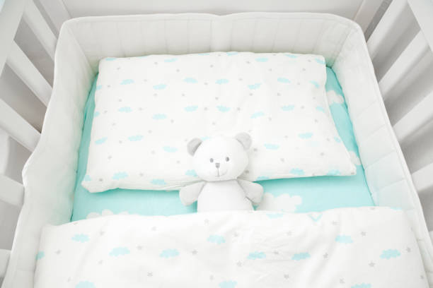 Small, white teddy bear in baby bed. Linen with clouds. Top view. Small, white teddy bear in baby bed. Linen with clouds. Top view. crib stock pictures, royalty-free photos & images