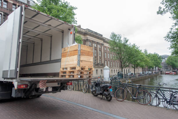 small white truck unloading on amsterdam canal bridge - lorries unloading stock photos and pictures