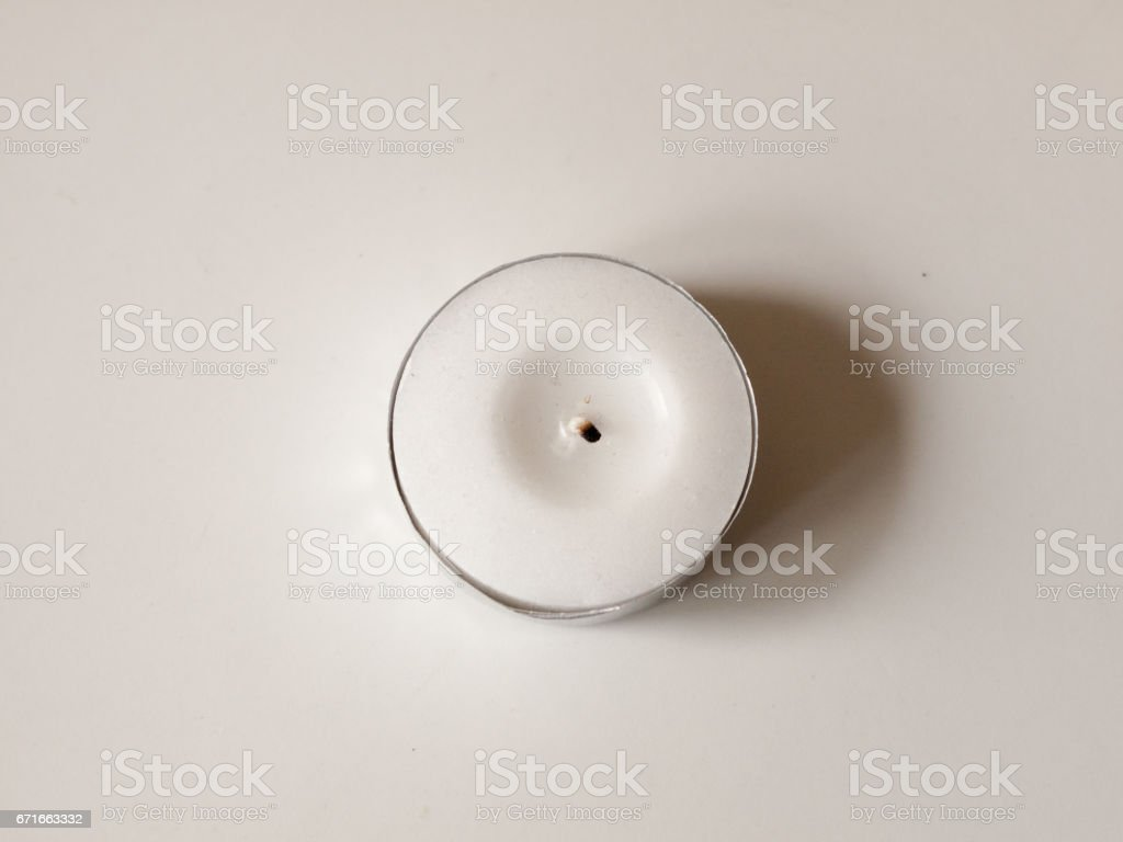 A Small White Wax Candle in A Circle Metal Base with Black Wick and No Flame, casting a Shadow on a White Background and Up Close Overhead in UK stock photo