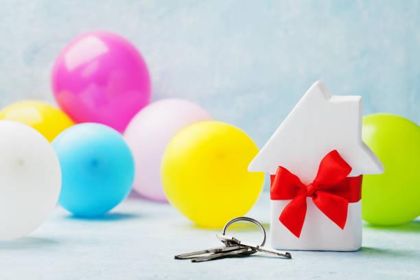 kleine weiße holzhaus dekoriert rote schleife band mit jede menge tasten und ballons. einweihungsparty, geschenk, umzug, immobilien oder kauf ein neues wohnkonzept. - schlüssel dekorationen stock-fotos und bilder