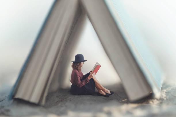 kleine Frau liest ein Buch-Gesetz geschützt durch ein Haus aus ein riesiges Buch – Foto