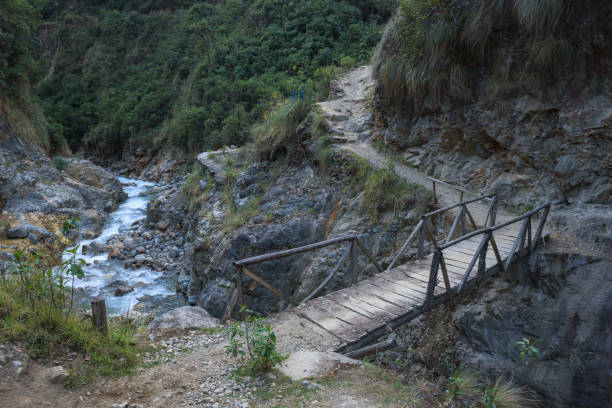 Small wooden bridge crossing a river along the Salkantay Trail stock photo