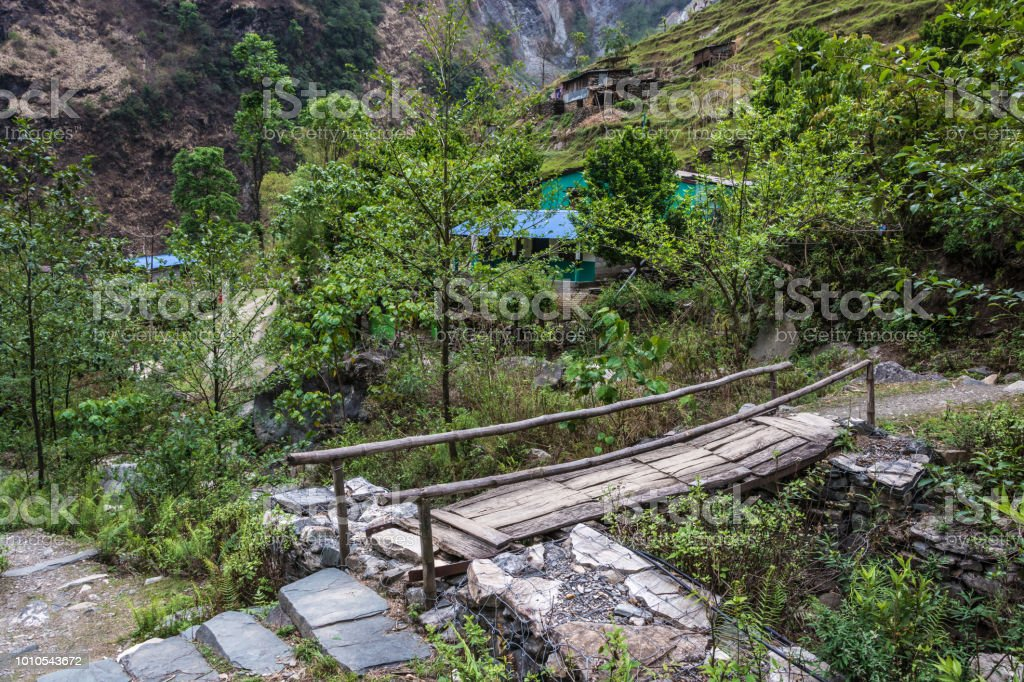 A small wooden bridge on a mountain path in Nepal. стоковое фото