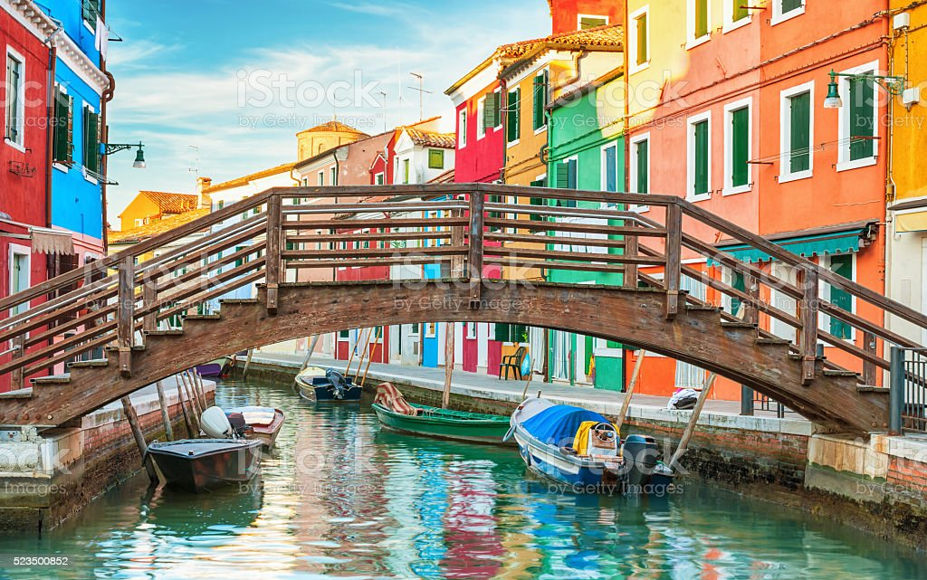 Small wooden bridge over a canal in Burano, Italy. stock photo