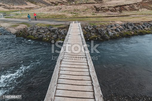 Small wooden bridge in Iceland. Two women on the horizon.