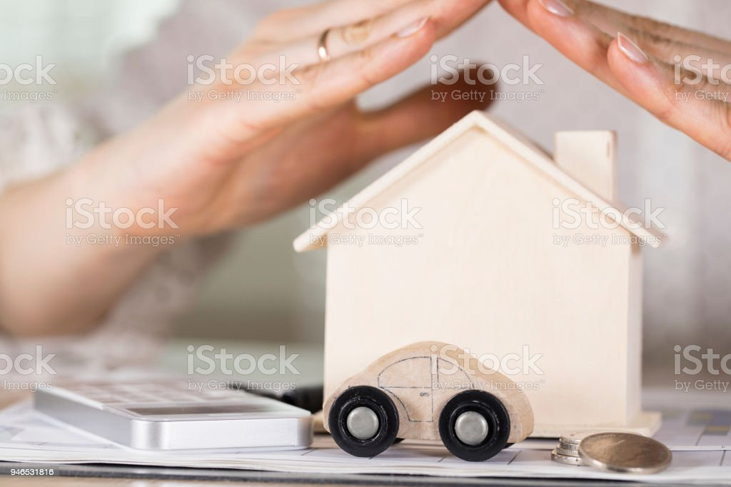 Small wooden car in front of a wooden house. stock photo