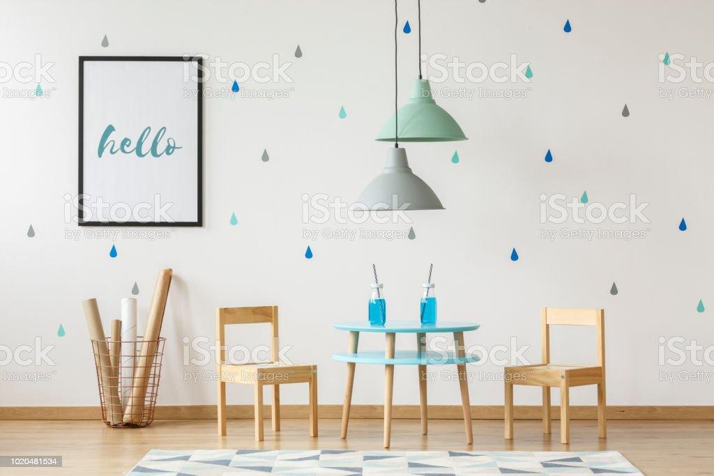 Cadeiras de madeira e mesa posta para crianças e mock-up cartaz em uma parede branca com papel de parede no interior de um quarto pré-escolar com elementos de azuis e verdes - foto de acervo