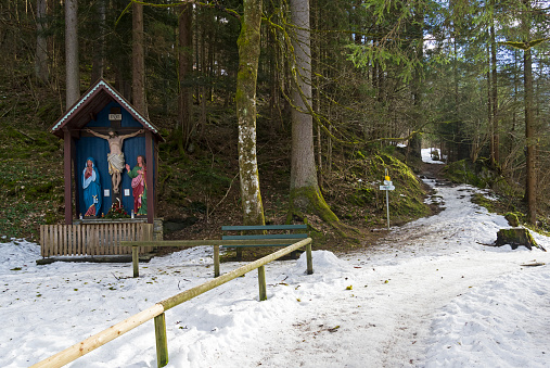 A small wooden chapel with a crucifix near the mountain path.