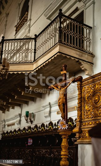 A small wooden cross with jesus statue on a gold stand. Small vintage balcony at the center stage of the church.