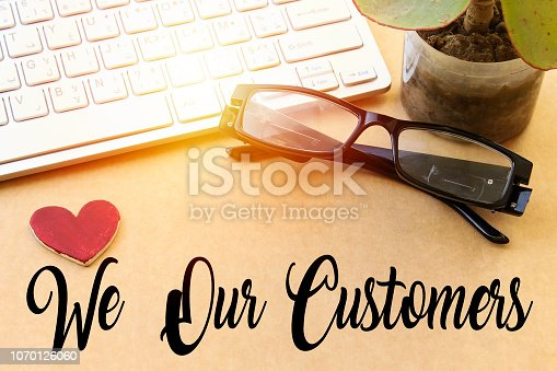 istock small wooden heart paper, white keyboard and eye glasses, succulent plant on wood table, We love our customers concept 1070126060