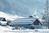 Winterly landscape in Upper Austria at world heritage site of Salzkammergut. Focused on first house.