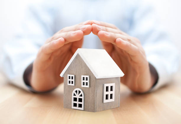 Small wooden house covered by hands stock photo