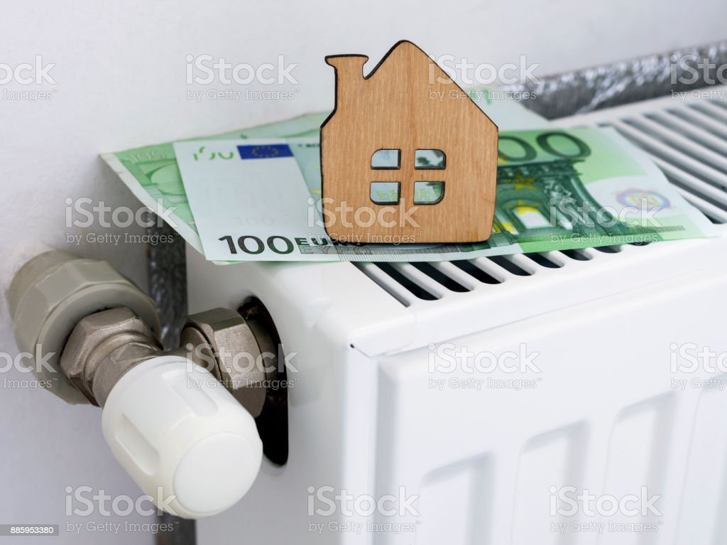 A small wooden house on the background of euro banknotes and radiator heating. Payment for heating in winter. Symbolic image, selective focus. stock photo