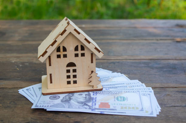 A small wooden house stands on 100 dollars banknotes. The concept of wealth, purchase, sale, rental of real estate, mortgage. Place for text. Copyspace stock photo