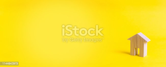 istock A small wooden house stands on a yellow background. The concept of buying and selling real estate, renting. Search for a house. Affordable housing, credit and loans. Investments in business. banner 1144642973