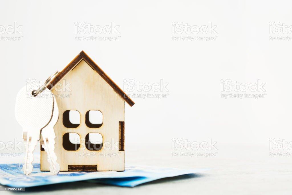 Pequena casa de madeira com chaves nele sobre o dinheiro com backgorund isolado - foto de acervo