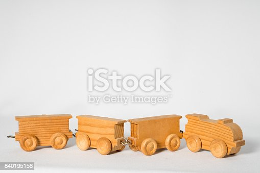 istock small wooden locomotive with three wagons, against white background 840195158